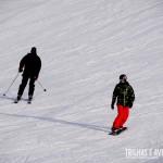 Esquiador e snowboarder descendo juntos a montanha