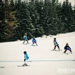 As crianças se amarram nas aulas em grupo das estações de ski