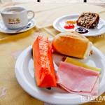 Frutas, frios, pães, bolos e geléias no café da manhã