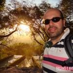 Sol se pondo entre as árvores no Parque das Fontes