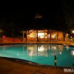 Vista noturna da piscina e restaurante