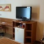 Mesa de trabalho e TV em frente a cama