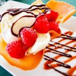 Sorvete na casquinha com frutas vermelhas e calda de chocolate