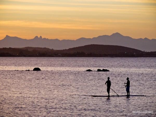 Amigos andando de SUP em Manguinhos durante o pôr-do-sol