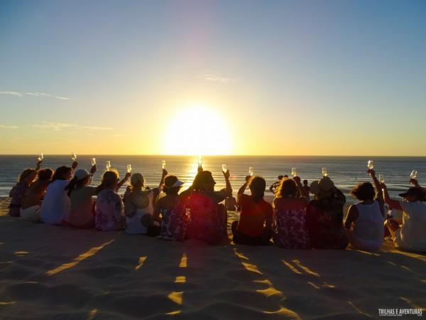 Grupo de amigas brindando ao pôr-do-sol em Jericoacoara